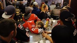 Une femme la tête posée entre ses bras dans un bar de la rue Elgin à Ottawa.