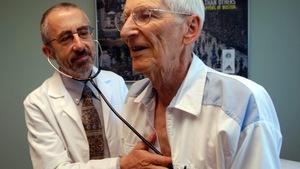 Un patient âgé est ausculté par un médecin.