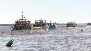 Des bateaux de pêche chargés de casiers à homard prennent la mer