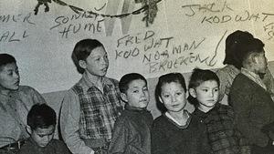Des enfants du pensionnat autochtone Baptist Mission School sont debout devant un mur un jour de Noël à Whitehorse.