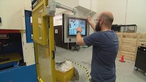 Un ingénieur de Laserax à Québec programme une machine destinée à faire du marquage au laser sur des pièces métalliques.