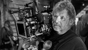 Pierre Mignot dans un studio portant une caméra sur son épaule.