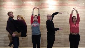 5 personnes qui ont l'air de bien s'amuser prennent la pose pour former les lettres PIF avec un point d'exclamation devant un mur de briques.