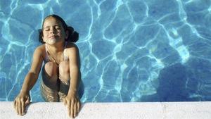 Une enfant se baigne dans une piscine.