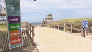 Un trottoir de bois pour se rendre à la plage. À droite, une affiche d'interdictions de breuvage, chien et autres. À gauche, une affiche pour la qualité de l'eau où il est inscrit Bon, passable, médiocre, fermé