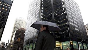 Photo d'un homme qui tient un parapluie dans le quartier des affaires de Toronto.