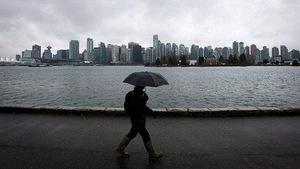 Photo d'un homme qui marche sous la pluie au parc Stanley, à Vancouver.