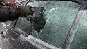 Un automobiliste dégivre la vitre de sa voiture couverte de glace.