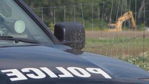 Une voiture de police avec en arrière plan une pelle mécanique