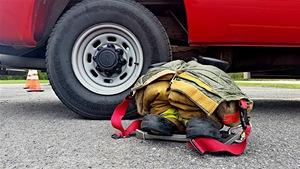Un pantalon et des bottes de pompier sont posés sur le sol à côté d'un camion de pompier.