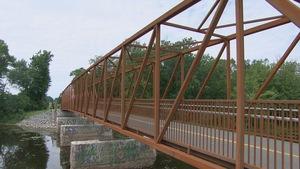 Un pont rougeâtre sur lequel passe une piste cyclable