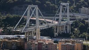 Un pont surplombant des bâtiments est photographié lors d'une journée ensoleillée. Une partie de ce pont est toutefois manquant.