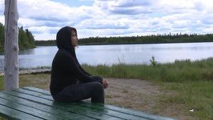 Une jeune femme au bord d'un lac