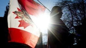 Photo d'un membre d'une Première Nation avec un drapeau canadien.
