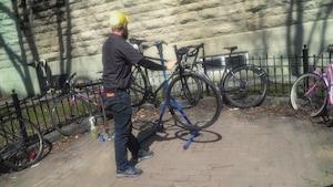 Un employé d'un atelier de réparation de vélo prépare une bicyclette sur la rue Saint-Jean à Québec.
