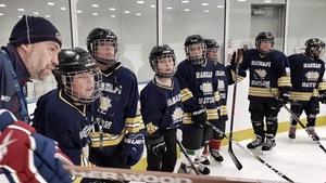 Joé Juneau donne ses instructions à de jeunes hockeyeurs de Kawawachikamach sur la patinoire locale.