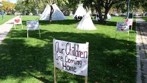 Des tipis et affiches installés dans un parc au Manitoba