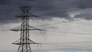 Pylône d'électricité avec des nuages menaçants en arrière-plan.