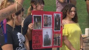 Une femme au sein d'une foule tient une pancarte demandant justice pour la mort de deux hommes.