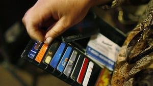 Une femme regarde ses cartes de crédit et d'identification dans son portefeuille