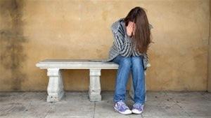 Adolescente découragée seule sur un banc.