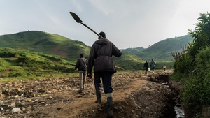 Rujana Sétuza, le pic sur le dos, se dirige vers la montagne en compagnie d'autres creuseurs.