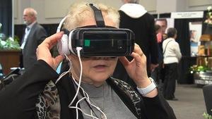 Une dame porte un casque de réalité virtuelle sur la tête, avec des écouteurs.