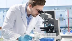 Un scientifique portant un sarrau blanc regarde dans un microscope