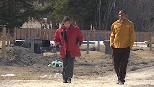 L'abbé et la paroissienne marchent ensemble dans le cimetière de la paroisse.
