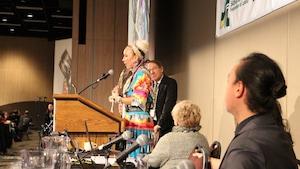 Une femme portant une robe à clochette colorée s'adresse à l'assistance au congrés.