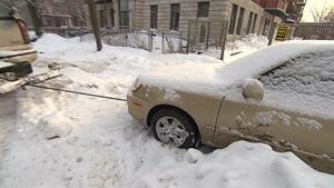 Une voiture se fait remorquer à Montréal durant une opération de déneigement.