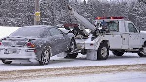 Une dépanneuse remorque une voiture.