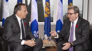 Le premier ministre François Legault (à gauche) discute avec le maire de Québec, Régis Labeaume (à droite), lors d'une rencontre à la salle Mistrale de l'Aquarium du Québec le 1er novembre 2018. Les deux hommes sont assis dans des fauteuils en cuir. Derrière eux, on aperçoit des drapeaux du Québec et de la Ville de Québec.