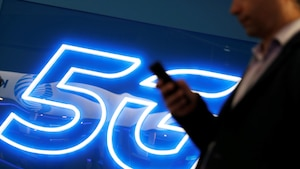 Un homme regarde son téléphone devant une enseigne lumineuse sur laquelle on peut lire « 5G ».