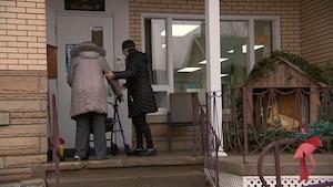 Deux femmes, de dos, entrent dans une résidence. On voit des décorations de Noël à l'extérieur.