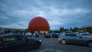 Le restaurant en forme d'orange géante, avec des voitures dans son stationnement.