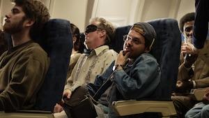 Le film 1991 prend l'affiche le 27 juillet. Le héros est en avion et semble réfléchir.