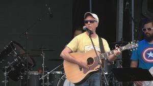 Zachary Richard chante et joue de la guitare sur scène