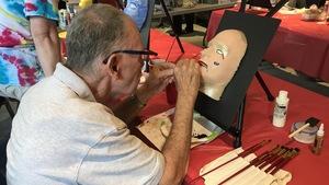 Un homme atteint de la maladie de Parkinson peint une tête de mannequin.