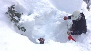 Un homme creuse dans la neige à la suite d'une avalanche.