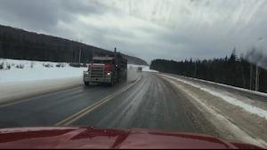 Deux camions se croisent sur une route à demi recouverte de glace.