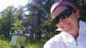 Marjorie Gobeil prend un selfie devant sa ruche sur un terrain proche d'une forêt.