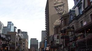 Des devantures de commerces rue Crescent, à Montréal, alors qu'on voit une murale de Leonard Cohen en arrière-plan.