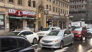 Des voitures sur la rue Sainte-Catherine devant des commerces