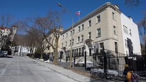 Deux piétons longent la grille devant le consulat de Russie à Montréal.