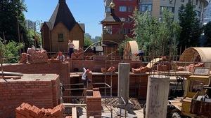 Des travailleurs s'affairent dans un chantier rempli de briques.