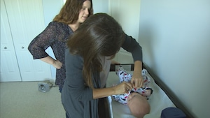 Une sage-femme épaule une jeune mère pour les soins de son bébé