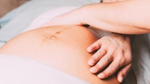 Deux mains de femme sur le ventre d'une femme enceinte couchée sur le dos.
