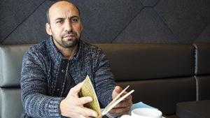 Saïd Akjour est attablé à un café de la région de Québec. Il tient entre ses mains un carnet dans lequel il rédige des poèmes.