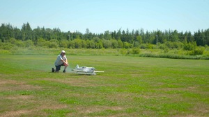 Un homme avec une casquette dirige un avion en modèle réduit sur le sol, dans un grand champ près d'une forêt de conifères.